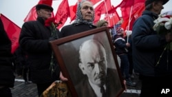 FILE - A woman carries a portrait of Lenin as she walks with the Communist Party members and supporters to place flowers at the Tomb of Soviet founder Vladimir Lenin, at Moscow's Red Square, Nov. 6, 2014. On Monday, Jan. 25, 2016, Russian President Vladimir Putin has criticized the regime of Soviet founder Vladimir Lenin and sharply denounced brutal repressions by the Bolshevik government.