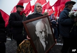 FILE - A woman carries a portrait of Lenin as she walks with the Communist Party members and supporters to place flowers at the Tomb of Soviet founder Vladimir Lenin, at Moscow's Red Square, Nov. 6, 2014.