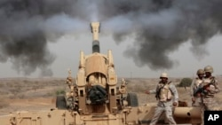 FILE - In this April 20, 2015 file photo, Saudi soldiers fire artillery toward three armed vehicles approaching the Saudi border with Yemen in Jazan, Saudi Arabia.
