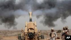 Des soldats saoudiens tirent en direction de trois véhicules militaires s'approchant de la frontière saoudienne avec le Yémen, le 20 avril 2015. (AP Photo/Hasan Jamali, File)