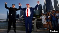 Howard, an Australian-Chinese impersonating North Korean leader Kim Jong-un, and Dennis Alan, impersonating U.S. President Donald Trump, meet at Merlion Park in Singapore, June 8, 2018.