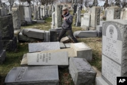 Rabbi Joshua Bolton of the University of Pennsylvania's Hillel center surveys damaged headstones at Mount Carmel Cemetery, Feb. 27, 2017, in Philadelphia.