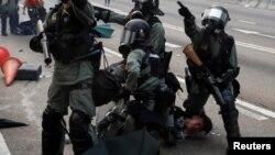 Polisi anti huru-hara Hong Kong menahan seorang demonstran anti pemerintah dalam aksi protes hari Minggu (29/9).