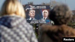FILE - A billboard showing a pictures of then-U.S. president-elect Donald Trump and Russian President Vladimir Putin is seen through pedestrians in Danilovgrad, Montenegro, Nov.16, 2016.