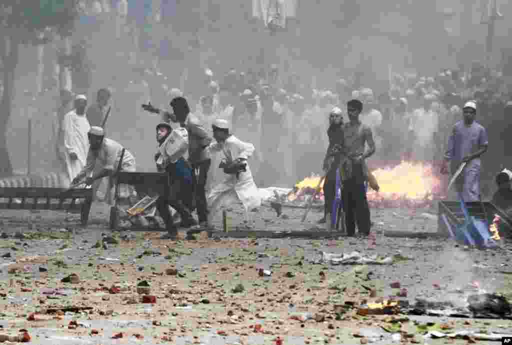 Bangladeshi protesters throw stones at policemen during a protest in Dhaka, Bangladesh, to demand that the government enact an anti-blasphemy law.