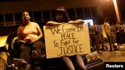 19일 미국 미주리주 퍼거슨 시에서 흑인 청년이 백인 경찰의 총에 맞아 사망한 사건에 항의하는 시위가 열린 가운데, 한 주민이 평화적인 시위를 촉구하는 문구를 들고 있다.