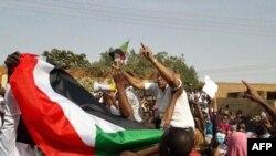 Rais wa Sudan wakiandamana na kupepea bendera ya taifa huko Omduuman.