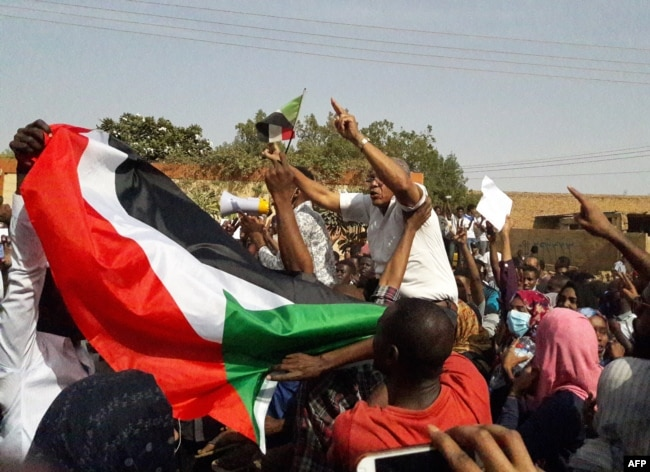 FILE - Sudanese protesters wave their national flag and chant slogans during an anti-government demonstration in the capital Khartoum's twin city of Omdurman on Jan. 31, 2019.