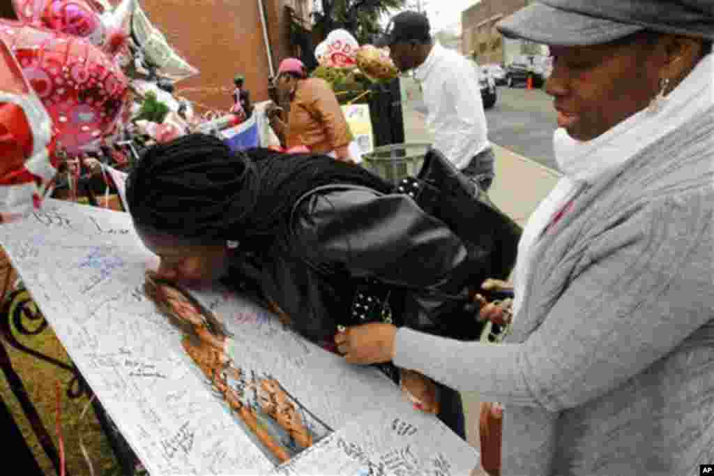 Yamda Johnson, kisses a signed photo of Whitney Houston as she and her friend Regina Kujemya both from Staten Island, N.Y., pay their respects at New Hope Baptist Church, in Newark, N.J., Wednesday, Feb. 15, 2012.