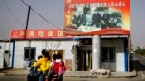 FILE - A Uyghur woman fetches schoolchildren as they ride past a picture showing China's President Xi Jinping joining hands with a group of Uyghur elders at the Unity New Village in Hotan, in western China's Xinjiang region, Sept. 20, 2018.