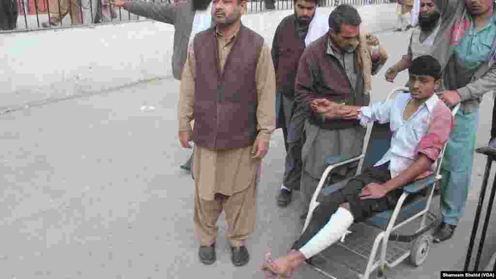 Un herido es transportado en silla de ruedas. (VOA)