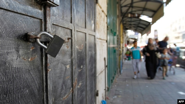 Across the entire Israeli-occupied Palestinian West Bank, businesses and shops closed as a sign of support for Palestinian prisoners on hunger strike being held in Israeli jails. Pedestrians walk by locked shops in Ramallah, June 8, 2014.