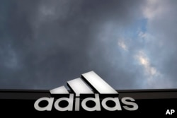 The logo of German sports equipment company adidas AG is illuminated at a factory outlet in Herzogenaurach, Germany, March 7, 2017.