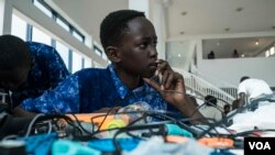 Aboubacar Savage, 14, from Gambia looks at a computer at the 2017 Pan-African Robotics Competition in Dakar, Senegal, May 19, 2017. (R. Shryock/VOA)