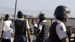 មន្ត្រីប៉ូលីសចាប់ឃាត់ខ្លួនបាតុករពីររូបក្នុងពេលតវ៉ាមួយនៅតំបន់ក្រីក្រស៊ីតេ សូឡេល នៅ Port-au-Prince ហៃទី ថ្ងទី២៤ ធ្នូ ២០១១។