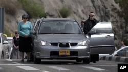 Israelis stand still beside their cars on highway as two-minute siren sounds in memory of Holocaust victims, Jerusalem, April 19, 2012.