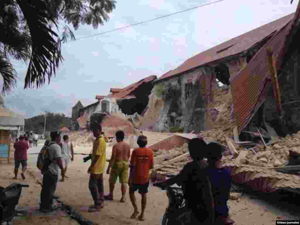 People walk near the damaged Loboc church, Bohol, Phillippines, Oct. 15, 2013. (Picture courtesy of Robert Michael Poole)