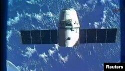 Pesawat kargo SpaceX Dragon terlihat di ujung lengan robot Canadarm2 stasiun antariksa internasional (ISS) dalam persiapan kembali ke bumi (31/5).