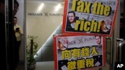 人们在莫萨克·冯赛卡律师事务所的香港地区总部附近示威,举着的标语牌上有英国首相卡梅伦和中国主席习近平的像(2016年4月12日)