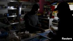FILE - A shopkeeper counts change by the light of a battery-powered lamp during a load-shedding electricity blackout in Cape Town, South Africa, April 15, 2015.
