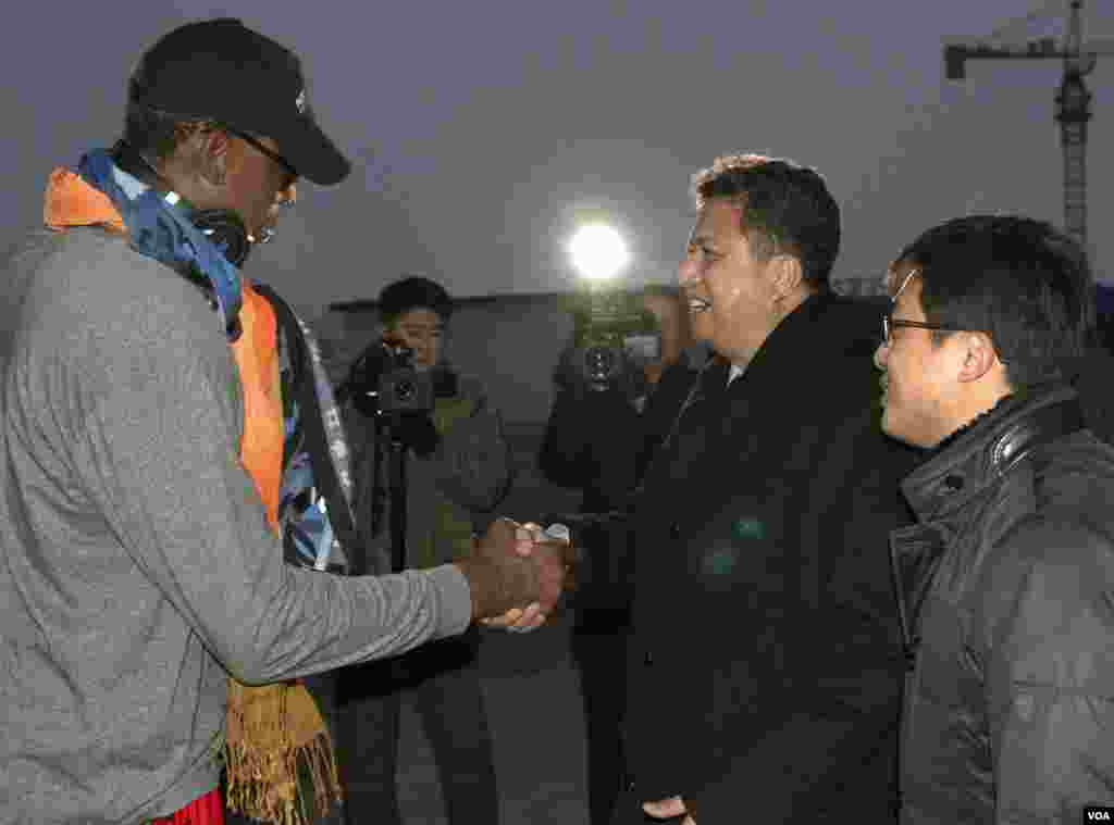 Former NBA basketball star Dennis Rodman shakes hands with Vice Minister of North Korea's Sports Ministry, Son Kwang Ho, as Rodman arrives at the international airport in Pyongyang, North Korea, Dec. 19, 2013.