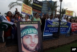 Activists of Pakistan civil society rally holding a picture of slain Kashmiri resistance leader Burhan Wani during an anti-Indian protest in Lahore, Pakistan on Aug. 2, 2016.