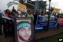 FILE - Activists of Pakistan civil society rally holding a picture of slain Kashmiri resistance leader Burhan Wani during an anti-Indian protest in Lahore, Pakistan, Aug. 2, 2016.