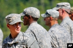 FILE – A female U.S. Army captain smiles as she stands in formation during an Army Ranger School graduation ceremony at Fort Benning, Georgia, Aug. 21, 2015.