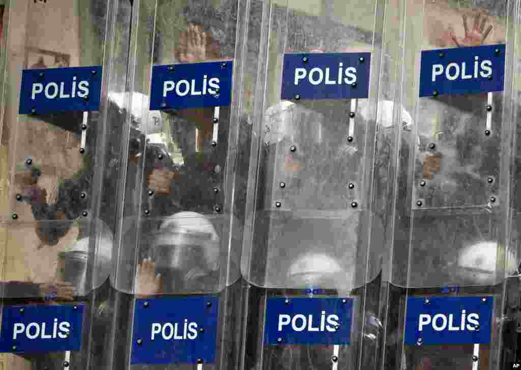Riot police press their hands onto their shields during clashes in Istanbul, July 8, 2013.
