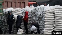 지난해 1월 북한 접경도시 신의주에서 주민들에게 중국을 통해 수입한 밀가루를 배급하고 있다. 압록강 건너 중국 단둥에서 바라본 모습. (자료사진)