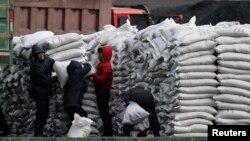 지난 1월 북한 접경도시 신의주에서 주민들에게 밀가루 포대를 나눠주고 있다. 압록강 건너 중국 단둥에서 바라본 모습이다. (자료사진)