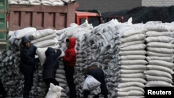 지난해 1월 북한 접경도시 신의주에서 주민들에게 밀가루 포대를 나눠주고 있다. 압록강 건너 중국 단둥에서 바라본 모습. (자료사진)