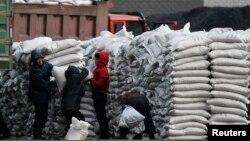 지난 2014년 1월 북한 신의주에서 주민들에게 밀가루 포대를 나눠주고 있다. 압록강 건너 중국 단둥에서 바라본 모습. (자료사진)