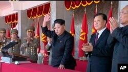 """金正恩(中)2015年10月10日同劉雲山(右二)一道觀看北韓""""勞動黨""""建黨70周年閱兵式。"""