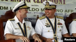 Philippine Navy Rear Admiral Leopoldo Alano (R) shares a light moment with U.S. Navy Rear Admiral William Merz during the opening ceremony of the Cooperation Afloat Readiness and Training (CARAT) 2015 at navy headquarters in Puerto Princesa city, Palawan on June 22, 2015