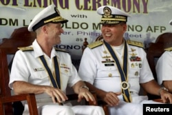 FILE - Philippine Navy Rear Admiral Leopoldo Alano (R) shares a light moment with U.S. Navy Rear Admiral William Merz during the opening ceremony of the Cooperation Afloat Readiness and Training (CARAT) 2015 at navy headquarters in Puerto Princesa city.