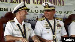 Philippine Navy Rear Admiral Leopoldo Alano (R) shares a light moment with U.S. Navy Rear Admiral William Merz during the opening ceremony of the Cooperation Afloat Readiness and Training (CARAT) 2015 at navy headquarters in Puerto Princesa city, Palawan
