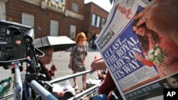 A news cameraman reads a newspaper across from St. Mary's Hospital's exclusive Lindo Wing in London, July 22, 2013.