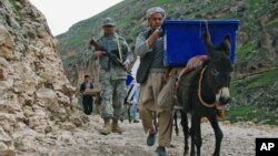 کارگران انتخاباتی از الاغ برای حمل صندوق های رای گیری به حوزه ها استفاده می کنند. مزار شریف، استان بلخ، ۳ آوریل ۲۰۱۴