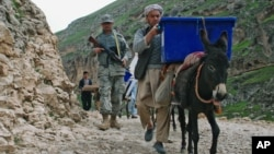 Afghan election workers use donkeys to transport ballot boxes and election materials to polling stations in Balkh province, Afghanistan, April 3, 2014.