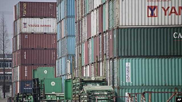 A forklift arranges the shipping containers near a port in Shanghai, China, March 2, 2011.