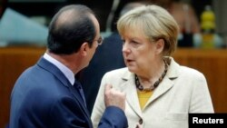 FILE - Germany's Chancellor Angela Merkel (R) and France's President Francois Hollande arrive for a working session during an EU summit in Brussels, Oct. 24, 2014.