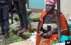 A woman shells peas at a street market in Abugarama, a mountain village near Bujumbura, Burundi, Dec. 14, 2015.