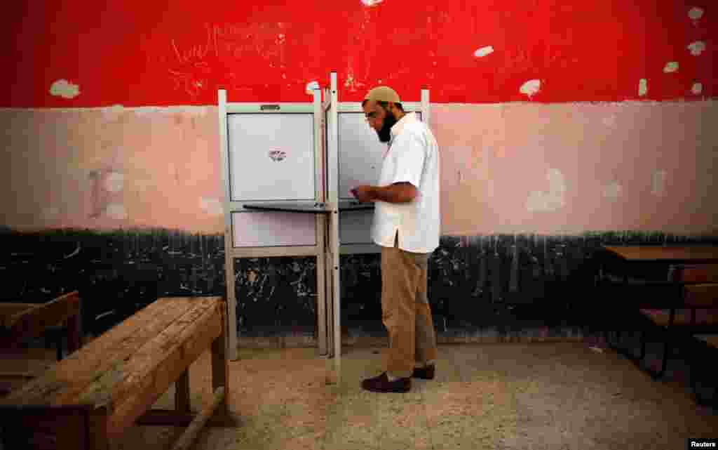 A voter prepares to cast his vote at a polling station in Cairo.