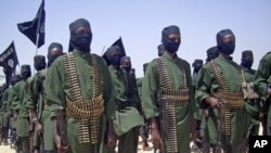 A February, 2011 photo shows al-Shabab fighters on parade with their guns during military exercises on the outskirts of Mogadishu, Somalia.