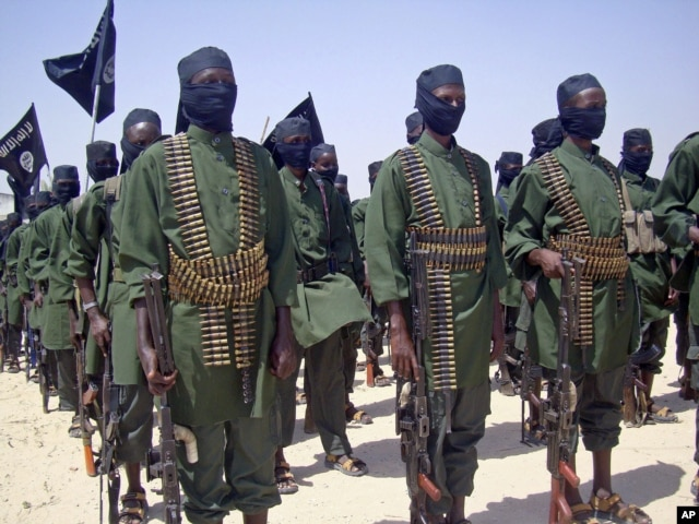 FILE - A February 2011 photo shows al-Shabab fighters on parade with their guns during military exercises on the outskirts of Mogadishu,Somalia.