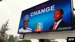 FILE - An electronic billboard displays a campaign poster of All Progressives Congress presidential candidate Mohammadu Buhari and running mate Yemi Osinbajo, who this week won Nigeria's democratic election.