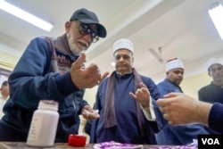 Voters dye their fingers with pink ink after casting their ballots to prevent voter-fraud in Cairo on April 20, 2019.