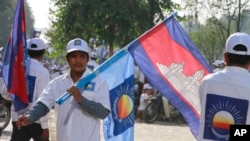 A supporter of the opposition Cambodia National Rescue Party holds the party flag together with a Cambodian national flag during an election campaign in Phnom Penh, Cambodia, June 27, 2013.