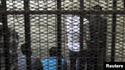 FILE - Defendants are seen standing behind bars in a Cairo court.